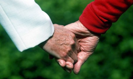 An older couple holding hands
